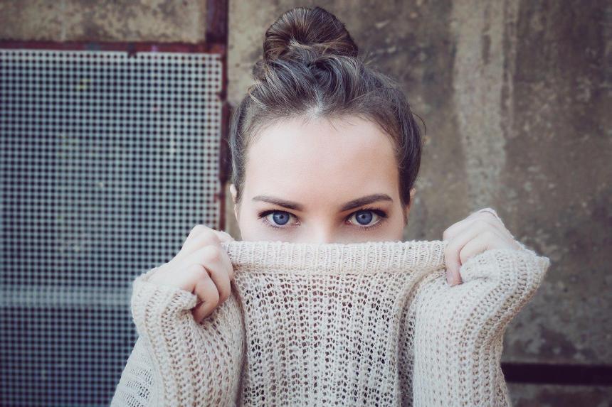 Gadis yang menyembunyikan setengah wajahnya dengan sweter rajutan.