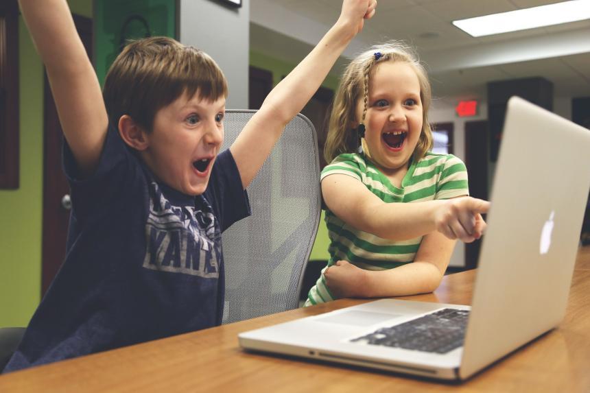 Glada barn vid dator.