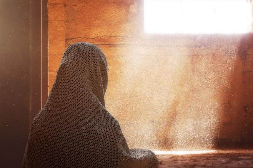 Islamic woman in front of a bright window opening.