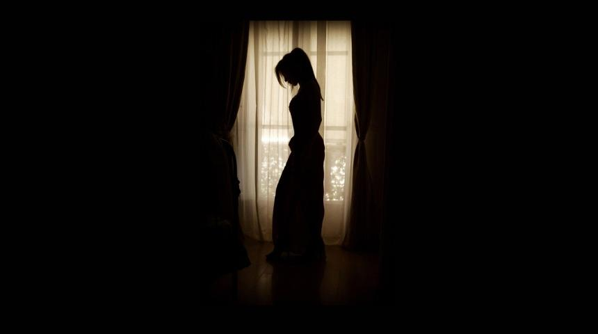 Kvinna i siluett framför ett fönster.