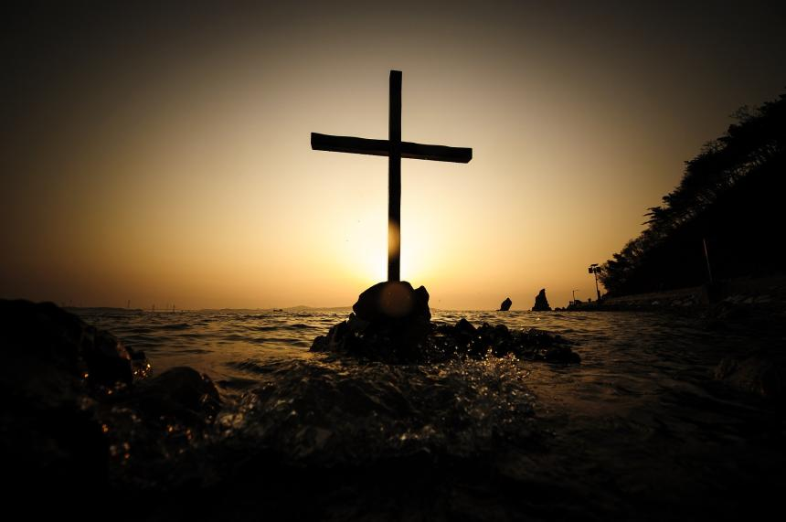 Cross on a rock in the sea and a sunrise.