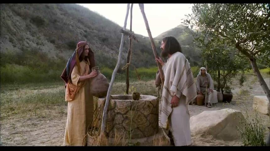 A woman and Jesus talk by a well.