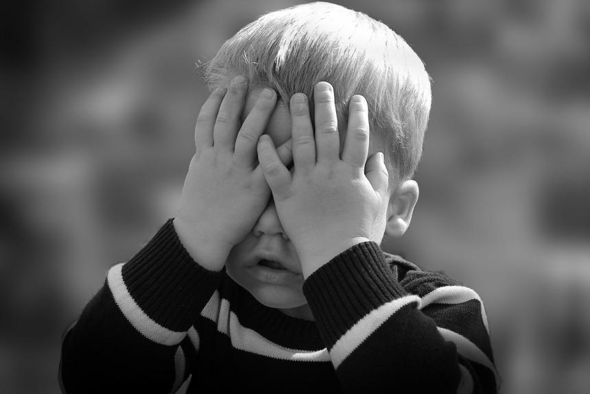 En pojke har sina händer framför sina ögon.