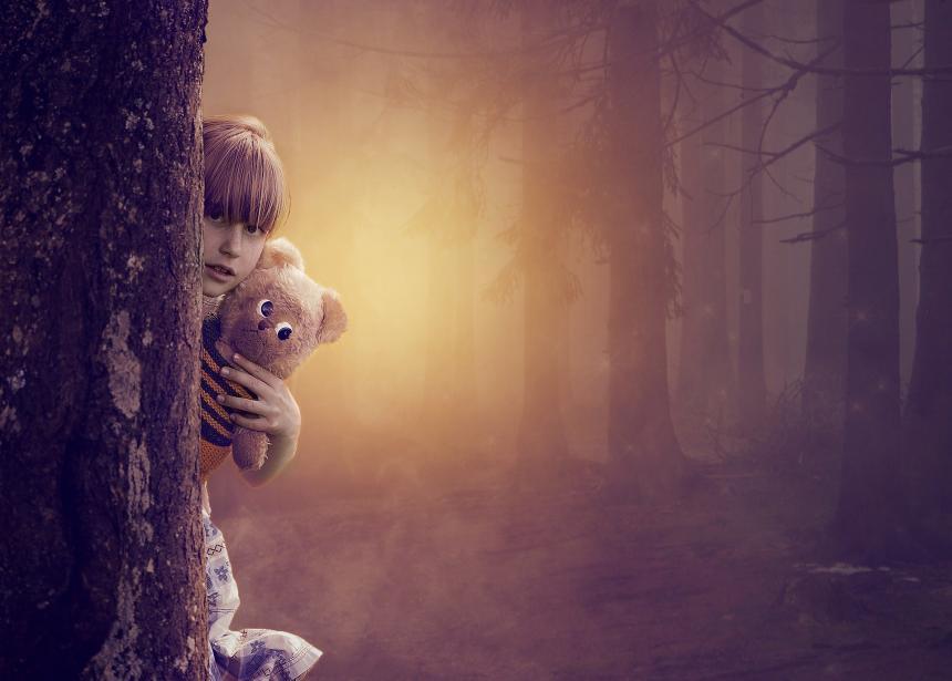 Girl with teddy bear hidden behind a tree.