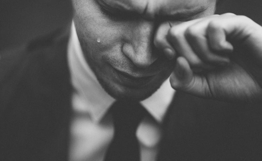 En man torkar sina tårar.